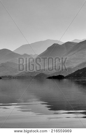 Reflections of the misty mountains over the wavy water surface, lake Skadar in Montenegro