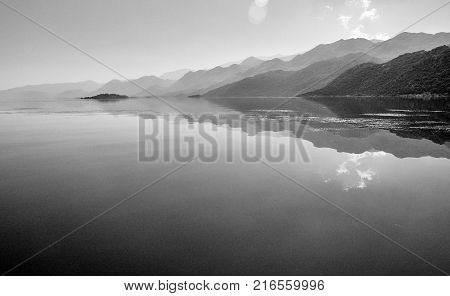 Reflections of the hills on water surface, lake Skadar in Montenegro