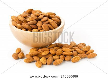 Heap of shelled almond kernels in wooden bowl over white background