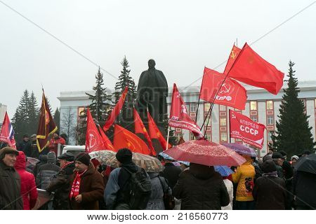 IZYUM Russia - November 7 2017. Red flag of Communist party of Ukraine against a monument to Lenin. Monument to Vladimir Ulyanov Lenin and flag of Communist party of Russia.