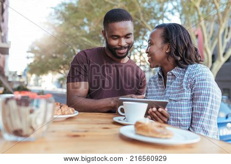 Smiling young African couple using a digital tablet together at a sidewalk cafe table while out on a coffee date