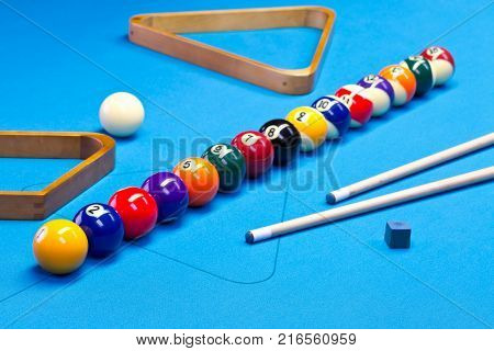 Billiard pool game balls lined up on billiard table with blue cloth with cues racks and chalk