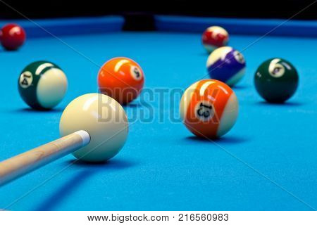 Billiard pool eightball taking the shot on billiard table with blue cloth selective focus on white ball