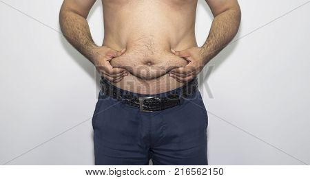 Young man hands holding belly fat. Young man show belly fat.