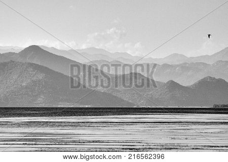 Landsape photograph of mountains over the lake Skadar in Montenegro, with one bird flying over