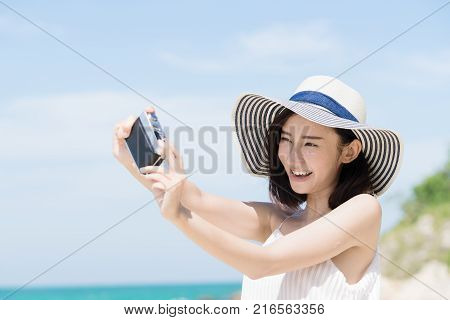 Young asian woman selfie by camera on the beach with sunny day. Happy girl selfie and smile with blue sky. Travel and lifestyle summer concept.