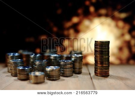 business leadership. Gold coins pile taller than other silver coin piles. Saving business investment concept. Gold light background.
