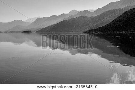 Mountains reflections in water, lake Skadar in Montenegro