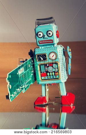 Tin Toy Robot Carries Computer Circuit Board, Artificial Intelligence Concept