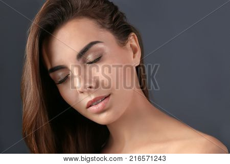 Beautiful young woman with eyelash extensions on grey background