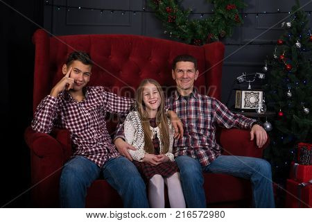 Joyful father with teenage daughter and son are sitting in front of a Christmas tree in anticipation of a merry Christmas.