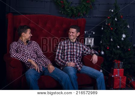 Cheerful Father And Son Are Sitting In Front Of A Christmas Tree