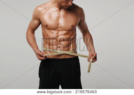 Bare-chested muscular man measuring his waist with measuring tape.