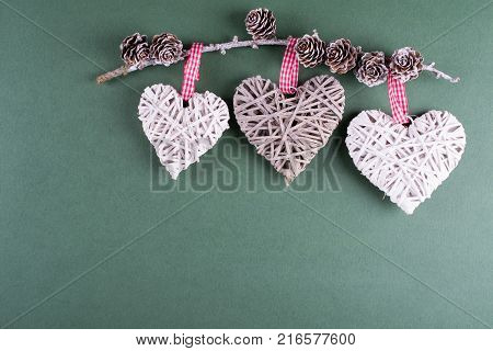 Christmas winter composition with handmade decoration. Heart-shaped décor. On green bright background