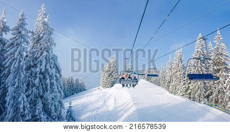 Four-person chair lift over of the ski piste among of the spruce trees in a ski resort in Carpathians