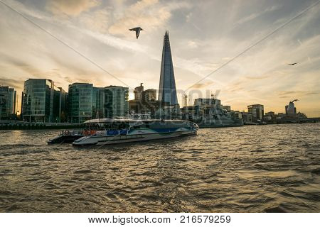 LONDON, UK - October 17th, 2017: The Shard building view from Thames riverside with river cruising ships in view, sunsetl with seagulls flying around.