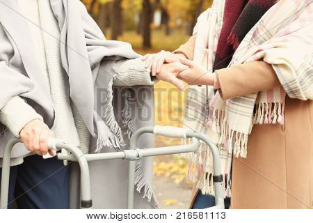 Senior woman with walking frame and young caregiver in park, closeup