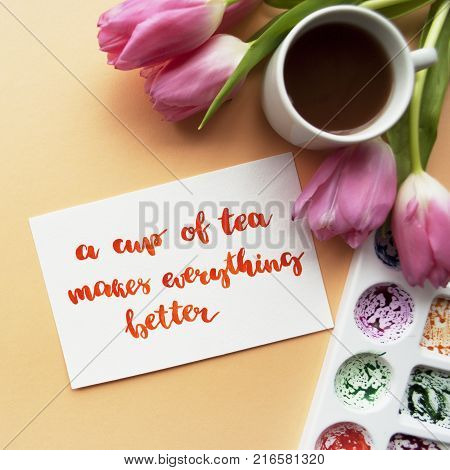 Coffee mug watercolor palette pink tulips on a peach background. Inspirational quote a cup of tea makes everything better written in calligraphy style with watercolor. Creative flat lay