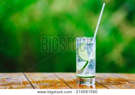 Glass glass. Lime. Mineral water with ice. Cocktail straw. A green backgroundA green background