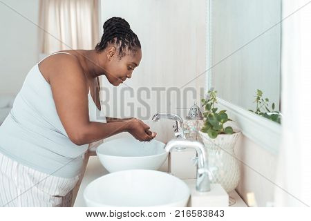 Young African woman washing her face wth water while standing over the basin in her bathroom in the morning