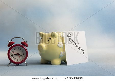 Piggy bank money box with the word pension and a small alarm clock, taken on a blue background