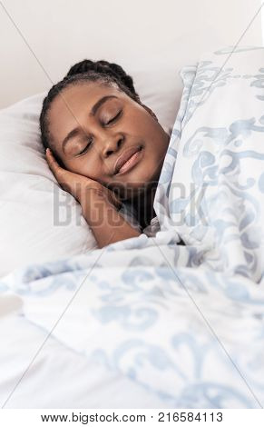 Young African woman fast asleep under the covers of her bed at home in the early morning poster
