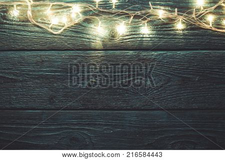 Image of green wooden table with burning New Year's garland.