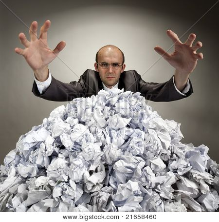 Serious Businessman Reaches Out From Crumpled Papers