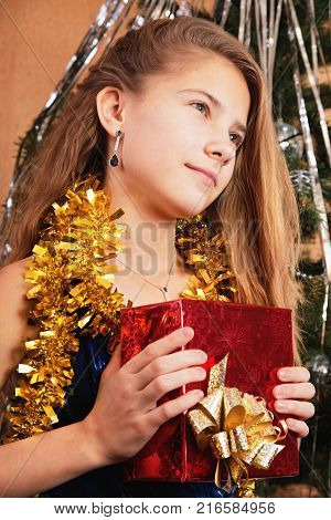 A teenage girl received a Christmas present and fantasizes about its contents. In the background is a Christmas tree