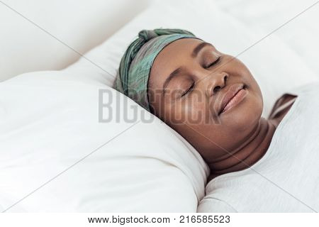 Young African woman wearing a headscarf sleeping peacfully in her bed at home in the early morning