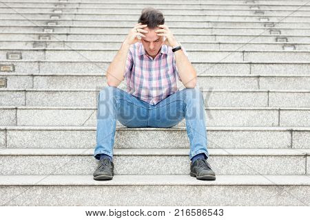 Portrait of tensed young man leaning head on hands and sitting on stairway outdoors. Front view.