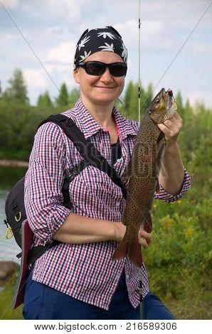 Fisherwoman caugth a big asiatic trout in wild Siberian river.