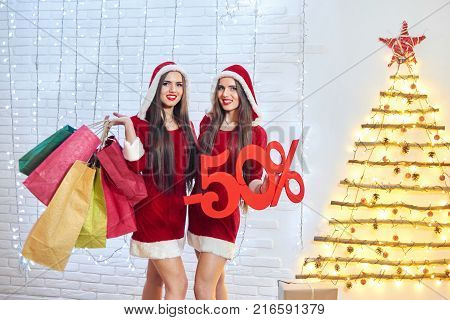 Horizontal shot of two happy young snow maidens in CHritmas outfits posing with shopping bags and -50 discount sign copyspace consumerism seasonal sale retail shopaholic x-mas. 2018