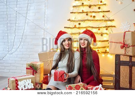 Shot of two happy twin sisters sitting at home surrounded by Christmas presents smiling cheerfully to the camra copyspace home coziness celebration people enjoyment surprise siblings concept. 2019