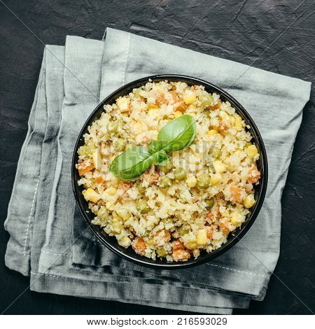 Top view of cauliflower rice with vegetables. Organic paleo Cauliflower Rice with corn, green peas and carrots on black concrete background. Copy space.