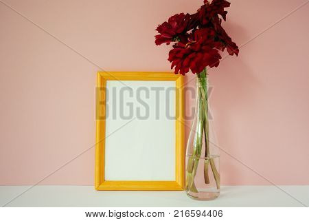 Yellow wooden photo frame mockup red cynicism in glass vase in front of pale pink pastel background