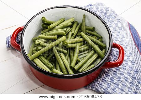 green beans in a water filled red and white enamel pot