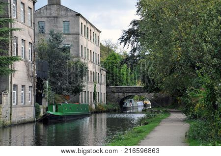 hebden bridge with the rochdale canal towpath boats and old buildings