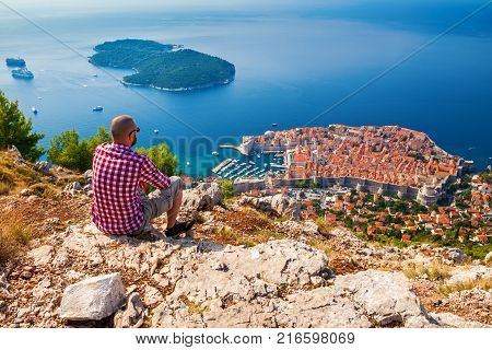 man looking down to the Old Town of Dubrovnik enjoying beautiful view sitting on the mountain above the city