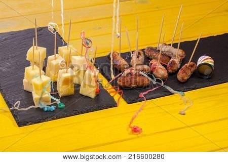 Sausages on sticks and cheese and pineapple nibbles. Leftover fun party food with party popper streamers on bright yellow table.