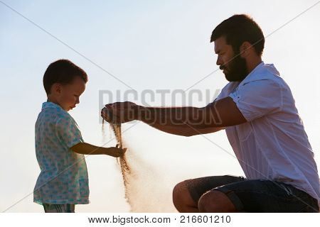 Happy family on sunset sea beach. Father baby son play with sand slipping through man hand fingers. Child catching falling sand. Active parents people outdoor activity on summer vacations with kids.