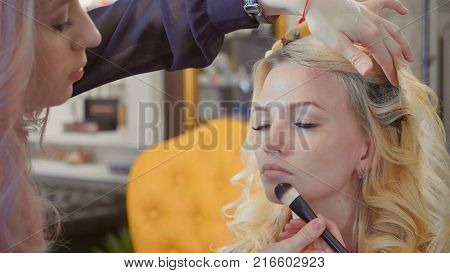 Close up of young girls's make-up process at beauty shop. Young visagiste applying concealer on model's face. Blonde woman sitting while artist is working via brush.