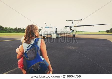 mother with little daughter coming to plane for boarding, family travel