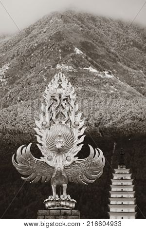 Dali Old Town with pagoda and phoenix statue before snow capped Cangshan in Yunnan, China.