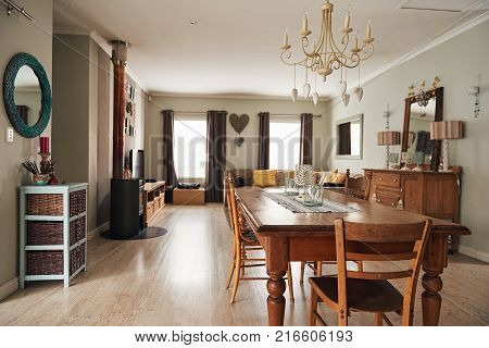 Interior of a contemporary suburban home decorated with country style dining table and modern sofa