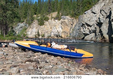 Inflatable catamarans on the bank of a mountain river. Chaya river, North Baikal Highlands, Siberia, Russia.