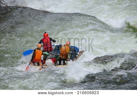Team of people on an inflatable catamaran rafting on white water. Chaya river, North Baikal Highlands, Siberia, Russia.