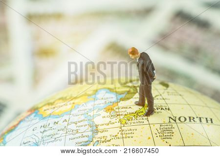 Miniature figure country leader man standing and looking at north korea map on globe as world critical nuclear missile war situation or war talk negotiation concept.