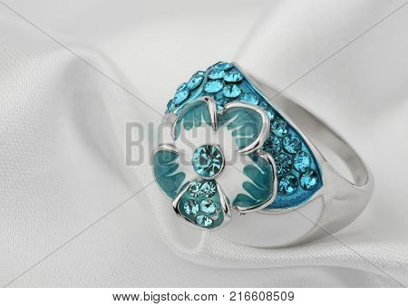 Jewelery ring with gems on white cloth background