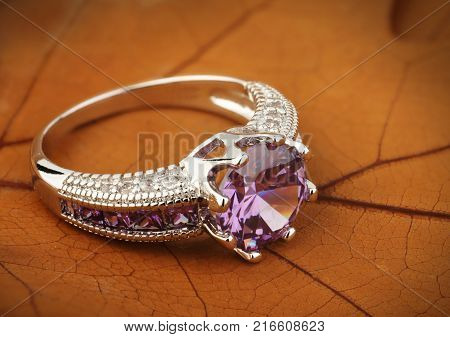 Jewelery ring with amethyst gemstone on yellow leaves background